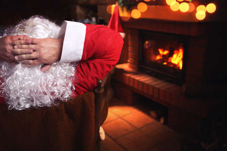 Santa Claus resting in a chair in front of a fireplace