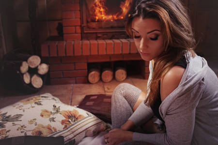 Young pensive woman in atmospheric climate in highland cottage Stock Photo