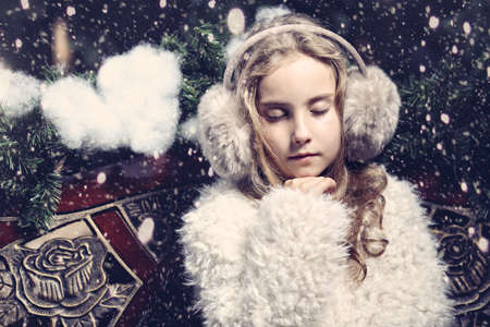 earmuffs: Young girl in earmuffs sitting on a winter day on the bench