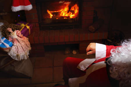 lapland: Santa Claus rests in hut with a fireplace Stock Photo