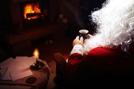 Santa Claus rests in hut with a fireplace and hot tea