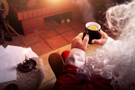 Santa Claus rests in hut with a fireplace and hot tea with lemon