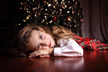 pobre: Muchacha pensativa joven tendido en la víspera de Navidad Foto de archivo