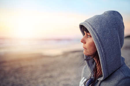 woman sunset: pensive woman in the hood Stock Photo