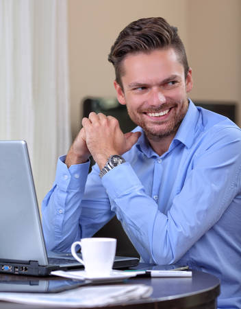 enterprising: Young businessman laughing at home with a laptop and coffee Stock Photo