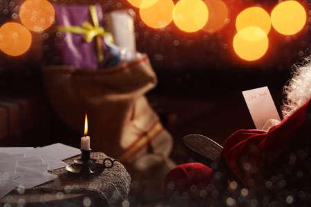 santa claus: Santa Claus reads the list at his home