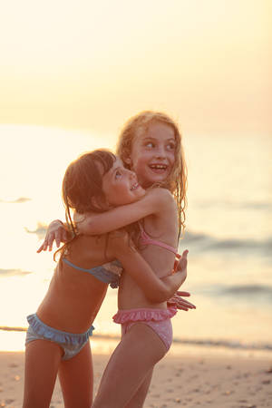 beach holiday: two happy girls in bathing suits snuggling up to each other on the seafront Stock Photo
