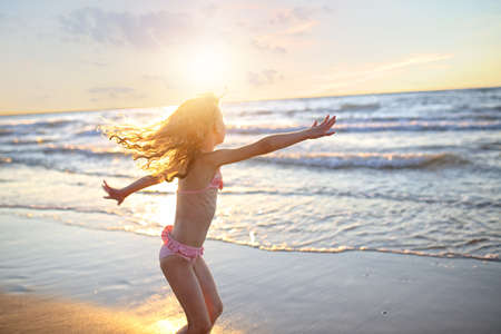 feet in water: happy little girl with curly long hair dancing in a swimsuit during sunset Stock Photo