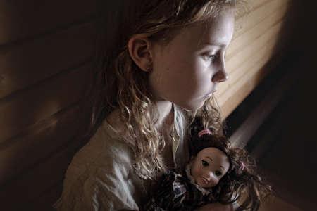 triste niña con el pelo rizado sentada confundirse con una muñeca Foto de archivo