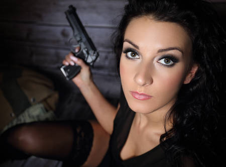 heist: Pretty girl with a gun Stock Photo