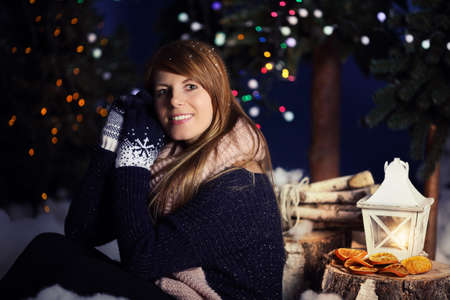 lantern: Smiling girl in gloves on a winter evening with lighted lantern