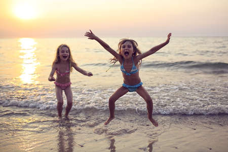 Two sisters playing on the beach at sunset