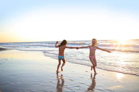 petite fille avec robe: Deux s?urs dansant sur la plage au coucher du soleil Banque d'images