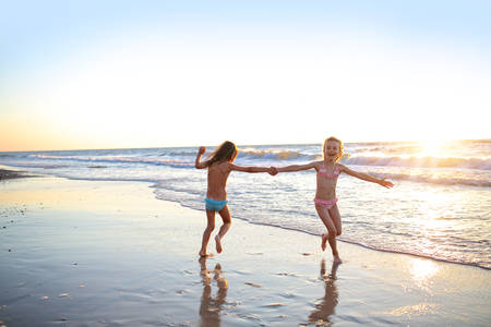 kids playing beach: Two sisters dancing on the beach at sunset