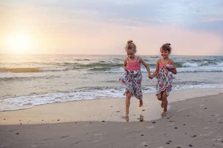 petite fille avec robe: Les jeunes filles qui courent pieds nus sur la plage Banque d'images