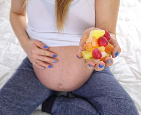 pregnant women donuts: Pregnant woman eats unhealthy sweets Stock Photo