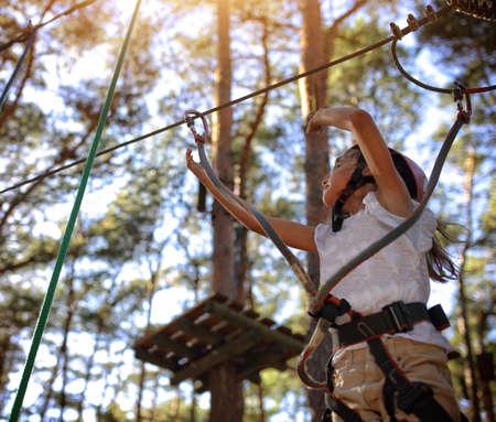 niño escalando: La niña en un casco en un parque de cuerdas