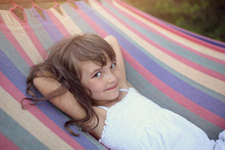 girl lying: Cute and happy girl lying on a hammock