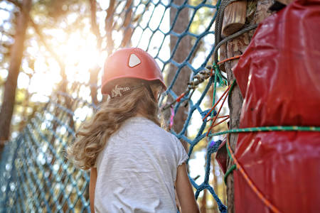 nervousness: Young girl climbing on the rope park Stock Photo