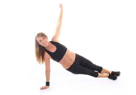 Athletic young woman practicing plank on white baclgr