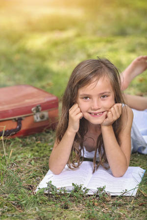 psicologia infantil: linda muchacha que lee un libro al aire libre