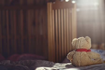 pedophilia: Teddy bear in an empty childs room Stock Photo