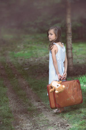 Young girl barefoot in the woods with a suitcase