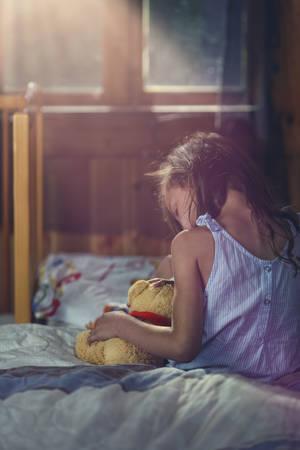 cuddles: distraught little girl cuddles a teddy bear