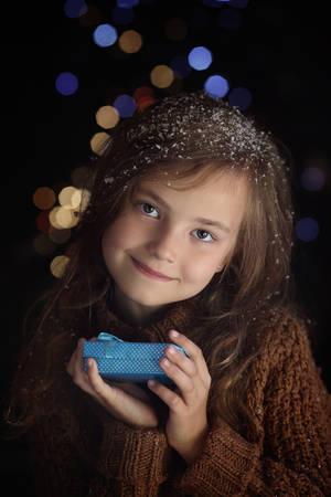 Little girl with a gift on the eve night Stock Photo