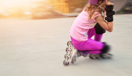 skate park: young girl rides on rollers in skate park