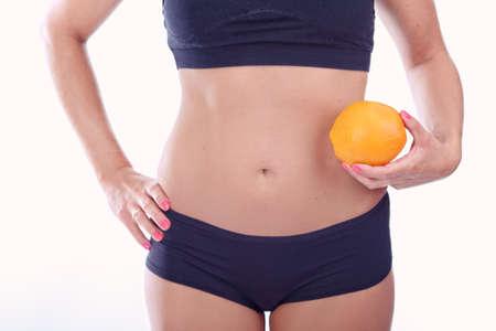 abdomen plano: mujer con un vientre plano que sostiene una naranja Foto de archivo