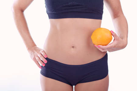 abdomen plano: woman with a flat stomach holding an orange Foto de archivo