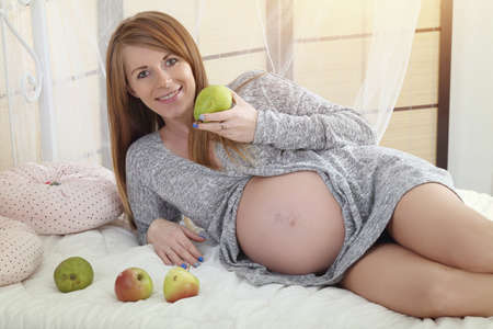 pregnant women donuts: Smiling pregnant woman eats healthy appl