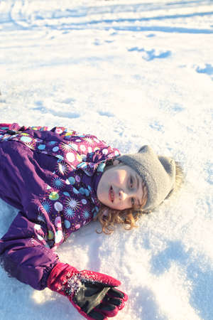 girls youth: cheerful young girl lies on the snow