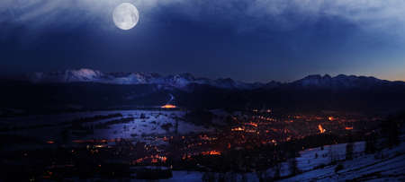 Magic night view on illuminated Zakopane city by moonlight buried