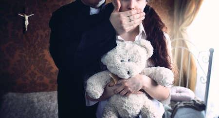 司祭は、若い女の子の口をカバーします。 写真素材