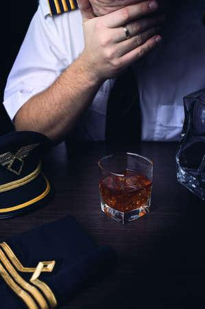 epaulets: pilot in uniform drinking alcohol