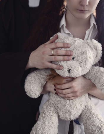 cleric: priest holding a teddy bear and young girl Stock Photo