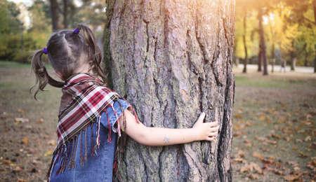 niños riendose: La chica joven que se abraza al árbol