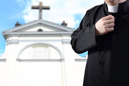 priest praying before the parish photo