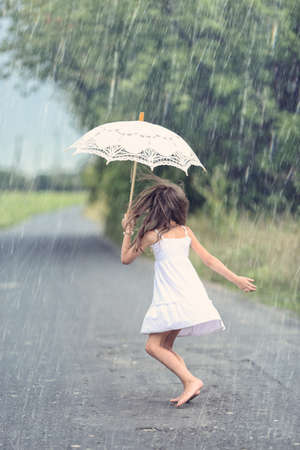 Joyful girl dance with umbrella in rain
