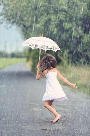 Vrolijk meisje dans met paraplu in de regen
