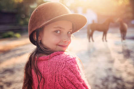 Young and smiling little girl in stables with horses