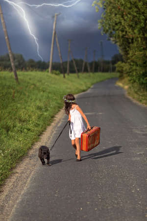 Young girl runs away from a storm with a dog and a suitcase