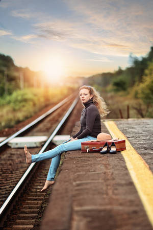 Woman sitting and meditating at a railway station Stock Photo