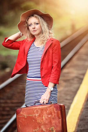 beautiful woman is waiting for the train at the train station