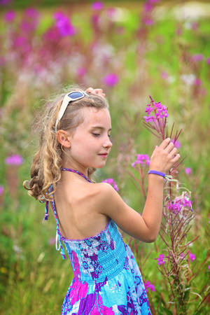 adorable girl enjoys life and gathers wildflowers