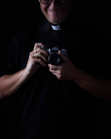 smiling priest with the camera