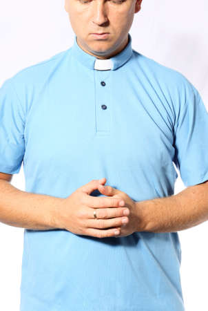 young priest is praying in a blue shirt