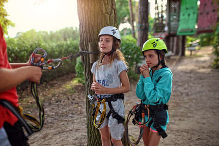 two young girls are training in a rope park